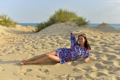 A young woman with a wreath of flowers on her head resting on a sandy beach royalty free stock photos