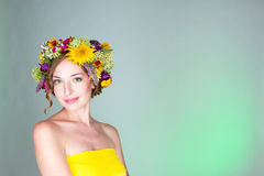A young woman in a wreath of flowers. Royalty Free Stock Image