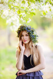 Young  woman in a wreath of flowers outdoors Royalty Free Stock Photo