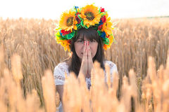 Young woman in a wreath of sunflowers folded his hands near the face and sitting in the wheat Stock Photo