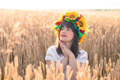 Young woman in a wreath of sunflowers folded his hands near the face and sitting in the wheat Royalty Free Stock Image