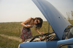 Young woman with wrench. Young woman with a wrench trying to fix a broken car Stock Photography