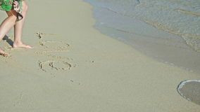 Young woman write love on sea sand. Rinse with sea water, Caribbean sea, stock video