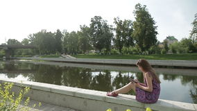 Young woman write something in her notebook on river bank in city park stock video