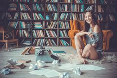 Young woman writer in library at home creative occupation laughing Royalty Free Stock Image