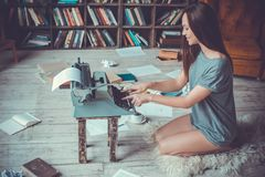 Young woman writer in library at home creative occupation typing inspired. Young female writer in library indoors working room messed with crumpled paper sitting Royalty Free Stock Photography