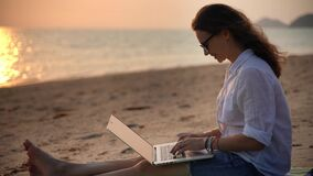A young woman writer sitting on the beach with her laptop and typing a text.