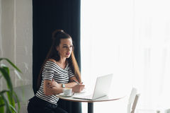 Young woman writer working at the cafe with notebook and laptop, drinking cappuccino. Young woman writer working at the cafe with notebook and laptop, drinking Stock Images