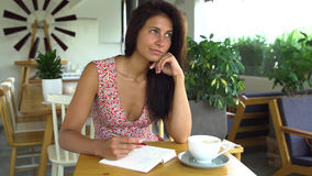 Young woman writer writes article in journal in cafe.