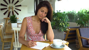 Young woman writer writes a book in cafe. stock photography