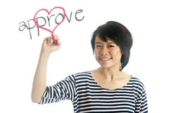 Young woman writes approve her heart Royalty Free Stock Image