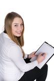 Young woman writes at a clipboard Stock Image