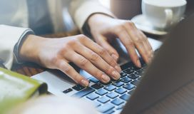 Young woman writes hands a text message on laptop keyboard with a empty blank screen monitor while having recreation time at home. Person with a cup of coffee royalty free stock photography