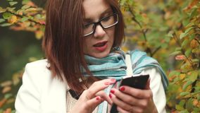 Young woman writes messages in the phone on a background of yellow leaves while walking in the autumn park stock video