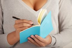 Young woman writes in the notebook Stock Photography