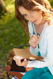 Young woman writes in notebook. Royalty Free Stock Photos