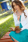 Young woman writes in notebook. Stock Photos