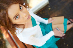 Young woman writes in notebook. Stock Photo