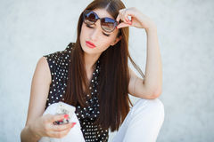 Young woman writes an SMS to your mobile phone Royalty Free Stock Photos