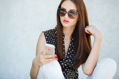 Young woman writes an SMS to your mobile phone Stock Photo