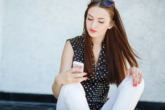 Young woman writes an SMS to your mobile phone Stock Photography