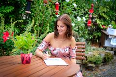 Young woman writes in the summer garden in a notebook or diary stock image