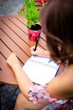 Young woman writes in the summer garden in a notebook or diary royalty free stock image