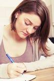 Young woman writes to black diary Stock Photos