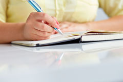 Young woman writes to black diary Stock Photo