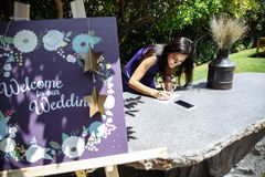 A young woman writes a wish for the newlyweds on the wedding day outdoors royalty free stock images