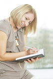Young woman writing Stock Image