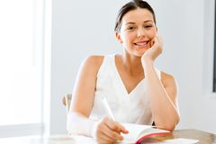 Young woman writing in an agenda at home or office Royalty Free Stock Images
