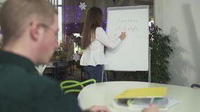 Young woman writing on the board strategy of work business, explaining her ideas to male colleague in the office. Man. Young woman writing on the board strategy stock footage