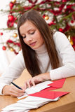 Young woman writing Christmas card Royalty Free Stock Photography