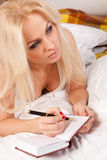 Young woman writing a diary while lying on th Stock Images