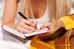 Young woman writing a diary while lying on th Stock Photos