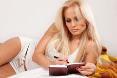 Young woman writing a diary while lying on th Royalty Free Stock Photography
