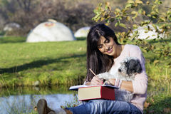 Young woman writing with her dog in an autumn park. Beautiful woman writing and reading a book in an autumn park with her dog royalty free stock photos