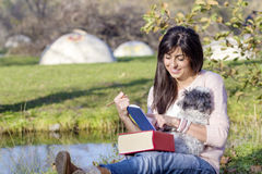 Young woman writing  with her dog in an autumn park Stock Photos