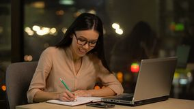 Young woman writing ideas into notebook, pondering plot of book, inspiration