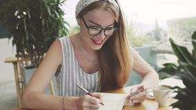 Young woman writing information from card to notebook . Female writing in cafe. stock video