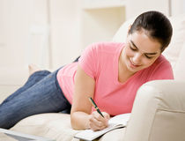Young woman writing in journal on couch Royalty Free Stock Images