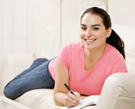 Young woman writing in journal on couch Stock Photo