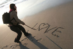 Young woman writing LOVE in the sand Stock Photography