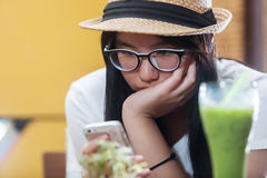 Young  woman writing message on cell phone. Young beauty woman writing message on cell phone in a cafe. Looking down Stock Photography