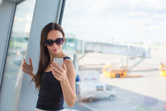 Young woman writing message on phone while waiting Royalty Free Stock Photo