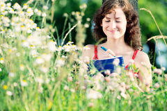 Young woman writing on nature, studying. Royalty Free Stock Images