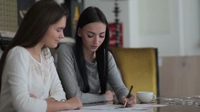 Young woman writing a note in business papers. Two young women sitting at a table in the office. Workers taking notes in business papers. Women are sitting at stock video footage