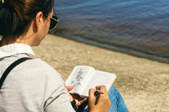 Young woman writing notebook list countries see beach sunny day. Young woman writing in notebook list of countries to see on the beach on sunny day. List of stock photo