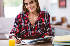 Young woman writing in notepad while holding digital tablet Royalty Free Stock Image